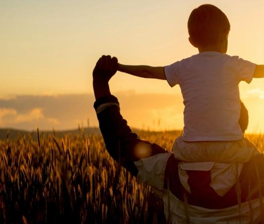 Un papa tenant son fils sur ses épaules